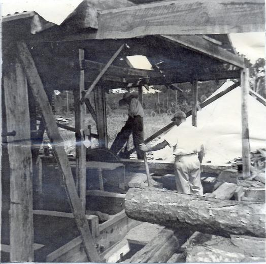Black and white photo of two men working in a saw mill
